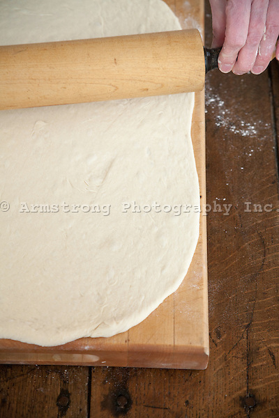 Pizza being rolled out on a wood cutting board using a rolling pin.