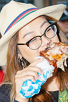 """Samantha Ouk, of West Des Moines, eats a turkey leg while listening to Democratic presidential candidate Tom Steyer speak at the Iowa State Fair in Des, Moines, Iowa, on Sun., Aug. 11, 2019. Ouk said that it was her first time at the Iowa State Fair and that she's had the turkey leg at other fairs, but """"It's really good here,"""" she said."""