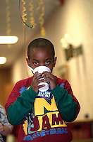 Thirsty boy age 6 at soup kitchen Thanksgiving dinner. Exchange Charities Minneapolis  Minnesota USA