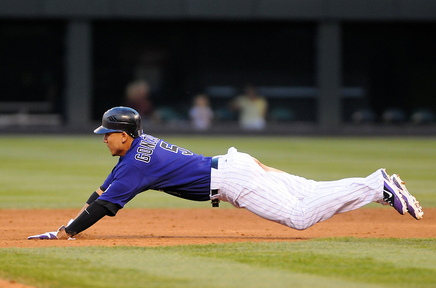 18 JULY 2011:  Colorado Rockies left fielder Carlos Gonzalez (5) slides headfirst safely into second base  during a regular season game between the Atlanta Braves and the Colorado Rockies at Coors Field in Denver, Colorado. The Braves beat the Rockies 7-4. *****For Editorial Use Only*****