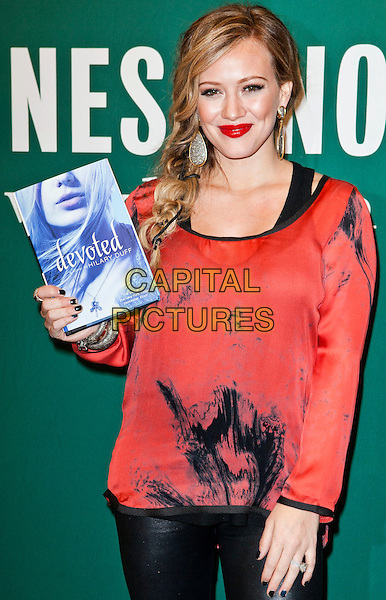 "Hilary Duff.Signs Copies Of Her New Book ""Devoted"" held at Barnes and Noble at The Grove, Los Angeles, California, USA, 14th October 2011..half length red top  black print lipstick make-up pregnant earrings dangly holding book novel   leather pants leggings pvc  .CAP/ADM/ES.©Emiley Scheich/AdMedia/Capital Pictures."