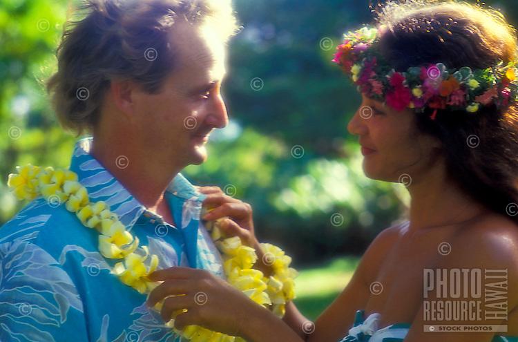Polynesian woman giving tourist flower lei