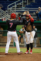 Batavia Muckdogs left fielder Michael Donadio (7) is congratulated by Albert Guaimaro (13) at home plate after he hit a home run in the bottom of the fifth inning during a game against the West Virginia Black Bears on June 18, 2018 at Dwyer Stadium in Batavia, New York.  Batavia defeated West Virginia 9-6.  (Mike Janes/Four Seam Images)