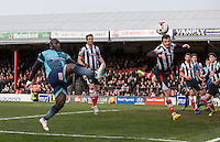 Gavin Gunning of Grimsby Town clears an Adebayo Akinfenwa of Wycombe Wanderers effort during the Sky Bet League 2 match between Grimsby Town and Wycombe Wanderers at Blundell Park, Cleethorpes, England on 4 March 2017. Photo by Andy Rowland / PRiME Media Images.