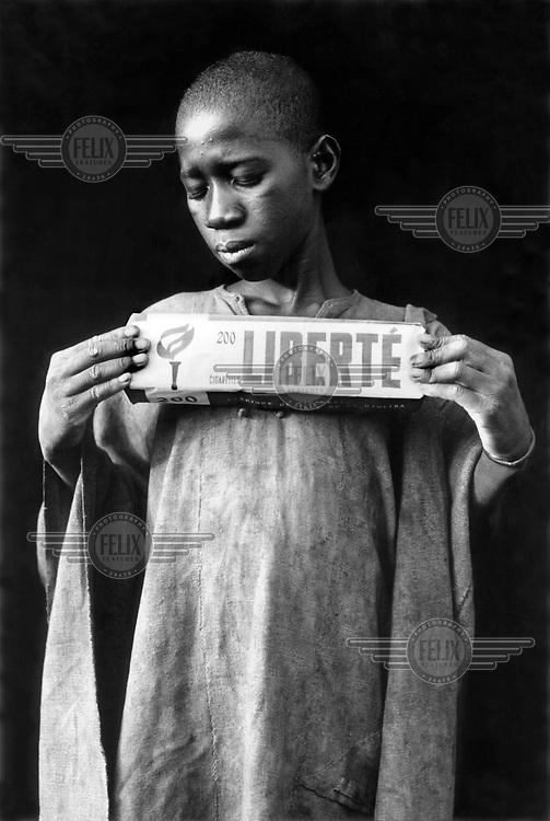 © Christien Jaspars / Panos Pictures..Diabolo, Mali...Bambara people of central Mali. Fommo holding a box of cigarettes.