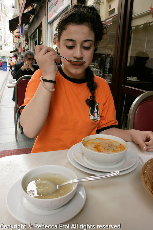 Turkish girl drinking iskembe corbasi (tripe soup) in Beyoglu, Istanbul, Turkey