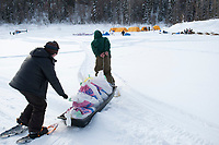 Checkpoint volunteers move musher's food bags from the plane to the Eagle Island checkpoint during Iditarod 2009