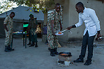 Cook serving breakfast to anti-poaching scouts before deployment, Kafue National Park, Zambia