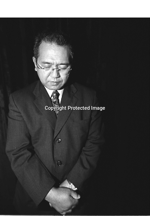 Kaoru Inoue prays before preaching at a Christian meeting at Queen Elizabeth Stadium  in Hong Kong, China. Inoue was once a member of the Japanese mafia Yakuza, and now a devoted preacher with the Protestant Evangelical group Mission Barabbas.<br />01-NOV-02