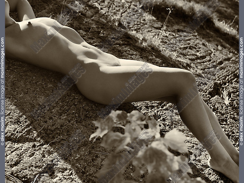 Nude woman lying on rocks in the nature