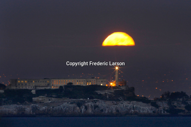The full moon made its way through the thin cloud cover and over the lighthouse on Alcatraz Island as seen from Crissy Field in the Presido of San Francisco, California.