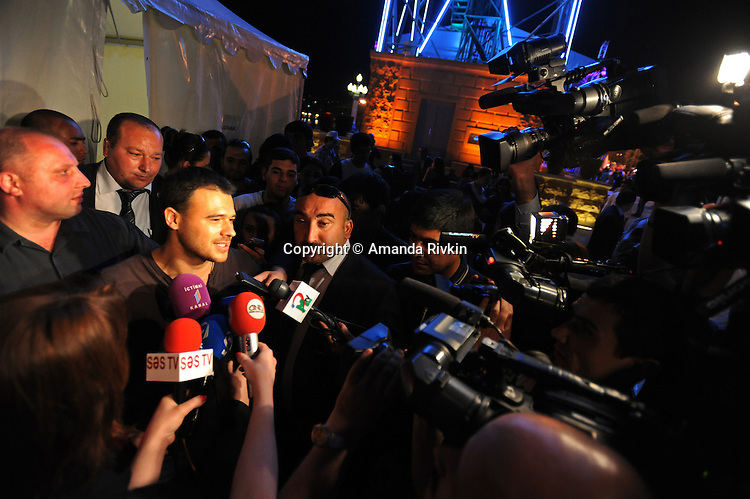 Emin Agalarov, the son-in-law of Azerbaijan's President Ilham Aliyev and the nation's top male pop star, speaks to the media after a performance on the Caspian seaside Bulvar at the Eurovsion Song Contest Fan Club concert on April 29, 2012.  Agalarov is married to Leyla Aliyeva, the eldest daughter of Azerbaijani President Ilham Aliyev who holds many hats in her own right, among them head of the Heydar Aliyev Foundation in Russia, editor of Baku Magazine, artist, and poet and Agalarov's father, Aras Agalarov, is a Russian billionaire oligarch of Azerbaijani origin in the retail and real estate development sectors, being the first to bring foreign luxury fashion brands to Russia after the collapse of communism and opening several gaudy malls and arenas in Moscow and elsewhere in Russia.