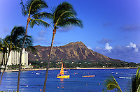 a colorful catamaran sails in front of Diamond Head