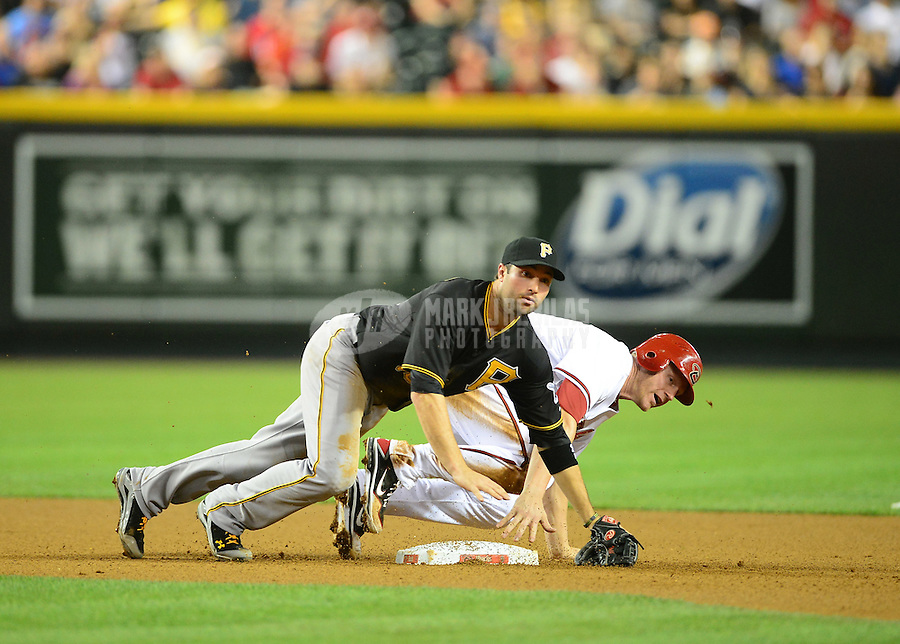 Apr. 17, 2012; Phoenix, AZ, USA; Pittsburgh Pirates second baseman Neil Walker falls over Arizona Diamondbacks base runner Lyle Overbay following a double play in the fourth inning at Chase Field. Mandatory Credit: Mark J. Rebilas-