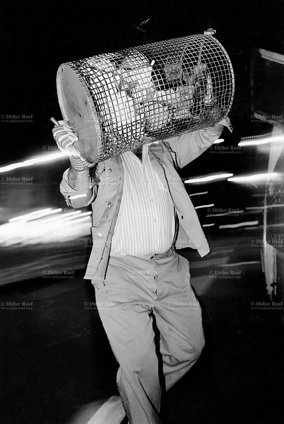 Switzerland. Geneva. Garbage collectors. Streets cleaning. A street sweeper (garbage man) carries in both hands a full garbage's bin. Night time. © 1991 Didier Ruef