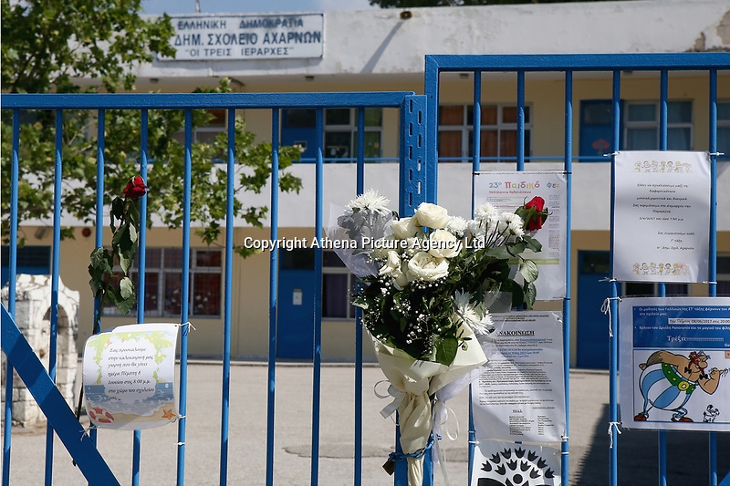 """Pictured: Flowers and tributes left at the gate of the 6th primary School in Acharnes, Athens, Greece. Saturday 10 June 2017<br /> Re: An 11 year old boy has been shot dead by a """"stray bullet"""" during a school celebration in Acharnes (Menidi) area, in the outskirts of Athens, Greece.<br /> Marios Dimitrios Souloukos """"complained to his mum"""" who works as a teacher at the 6th Primary School of Acharnes that he was feeling unwell, he then collapsed with blood pouring out from the top of his head.<br /> His mum tried to revive him assisted by other teachers while his schoolmates who were reportedly upset, were hurriedly removed by their parents.<br /> According to locals an ambulance arrived 25 minutes late.<br /> Hundreds of police officers have been deployed in the area and have raided many properties.<br /> Shells matching the fatal bullet which hit the boy on the top of his head were found in a house yard nearby.<br /> Local people reported hearing shots being fired at a nearby Romany Gypsy camp before the fatal incident.<br /> The area has been plagued with criminality during the last few years."""