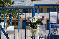 Pictured: Flowers and tributes left at the gate of the 6th primary School in Acharnes, Athens, Greece. Saturday 10 June 2017<br /> Re: An 11 year old boy has been shot dead by a &quot;stray bullet&quot; during a school celebration in Acharnes (Menidi) area, in the outskirts of Athens, Greece.<br /> Marios Dimitrios Souloukos &quot;complained to his mum&quot; who works as a teacher at the 6th Primary School of Acharnes that he was feeling unwell, he then collapsed with blood pouring out from the top of his head.<br /> His mum tried to revive him assisted by other teachers while his schoolmates who were reportedly upset, were hurriedly removed by their parents.<br /> According to locals an ambulance arrived 25 minutes late.<br /> Hundreds of police officers have been deployed in the area and have raided many properties.<br /> Shells matching the fatal bullet which hit the boy on the top of his head were found in a house yard nearby.<br /> Local people reported hearing shots being fired at a nearby Romany Gypsy camp before the fatal incident.<br /> The area has been plagued with criminality during the last few years.