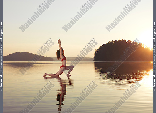 Young woman practicing Hatha yoga on a floating platform in water on the lake during misty sunrise in the morning. Yoga Low Lunge posture, Anjaneyasana. Muskoka, Ontario, Canada.