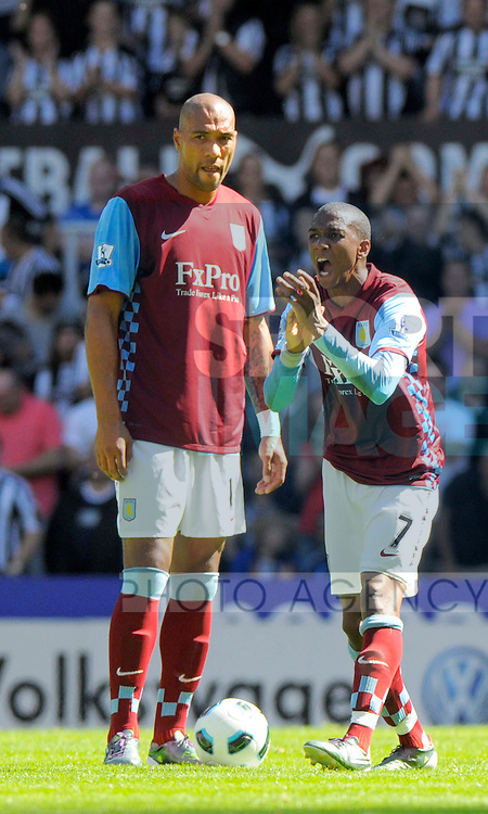 Aston Villa's Ashley Young (right) tries to urge his players on after conceding a second goal.