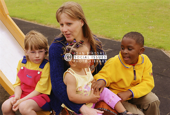Female child minder sitting with multiracial group of children in playground,