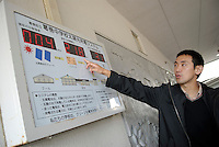 "Haruki Yoshizawa points at a display showing the rate of power generation from the solar panels at Kuzumaki Junior High School. Kuzumaki in Northern Japan bills itself as a town of ""Milk, wine and clean energy"". The 8000 population town has little local industry so Kuzumaki invited Japanese companies to set up wind, solar and biogas generating plants."