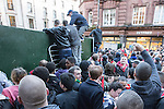 © Joel Goodman - 07973 332324 . 13/05/2013 . Manchester , UK . Fans use metal barriers as ladders to climb over barriers on Cross Street , opposite the Town Hall .  Manchester United fans jump on vans, jump over and tear down barriers erected around the Town Hall , during the Manchester United victory parade , this evening (13th May 2013) Photo credit : Joel Goodman