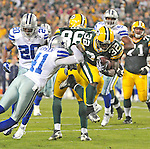 Green Bay Packers running back Brandon Jackson leaps through a tackle attempt by Terence Newman to score a touchdown against the Dallas Cowboys during the second quarter of the game at Lambeau Field on Nov. 7 , 2010.