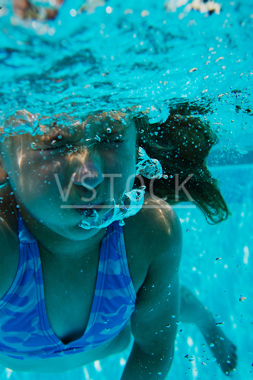 Girl (6-9) with eyes closed underwater