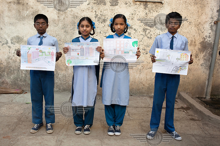 School children displaying drawings of how they would like Dharavi slum to look.