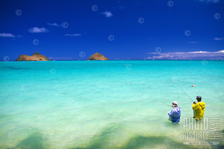 The beautiful Moku Lua islands stand majestic in the warm, blue waters near Lanikai Beach as fisherman(foreground) attempt to bring in the big one. Located on Oahu's windward side.