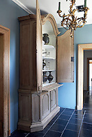 "In the ""Nattier""-blue entrance hall the interior of an antique oak cupboard has been limewashed to enhance a collection of Khmer vases, Liege glassware and Santa Lucia lanterns"