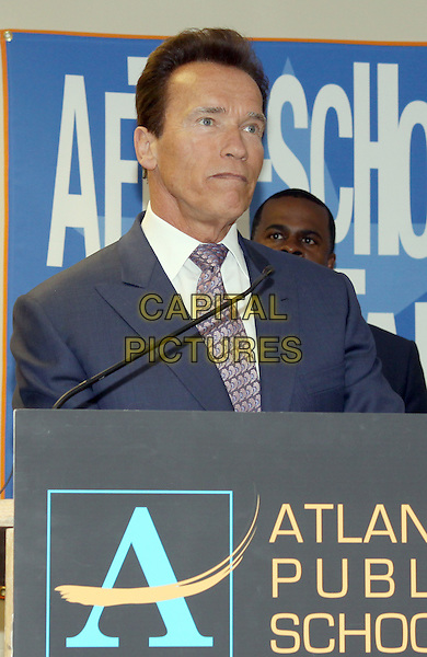 ARNOLD SCHWARZENEGGER.California Governor and actor Arnold Schwarzenegger, National Honorary Chairman of the After-School All-Stars program, attended the After-School Atll-Stars Atlanta Assembly Atlanta Assembly at the Joseph Emerson Brown Middle School, Atlanta, GA, USA..May 10th, 2010.half length grey gray suit pink tie podium blue speech microphone .CAP/ADM/DH.©Dan Harr/AdMedia/Capital Pictures.