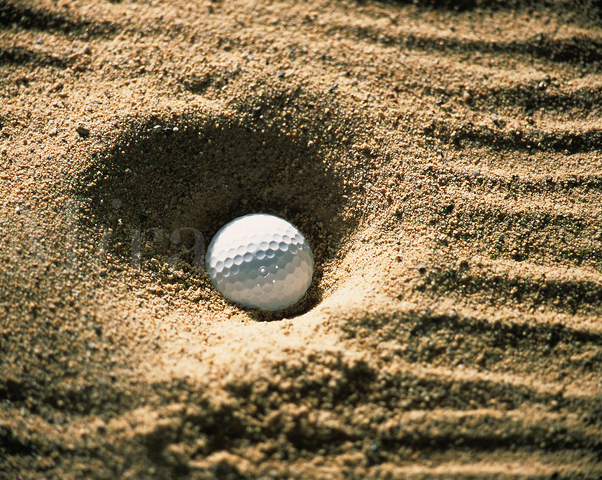 Detail view of a ball in a sandtrap.