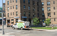 A Time Warner Cable truck parked outside one of the buildings in the Queensbridge North Houses in Queens in New York on Thursday, July 16, 2015. New York will be providing free broadband access to five housing projects in the city via a pilot program ConnectHome. Besides the Queensbridge North and South projects, Mott Haven and Red Hook East and West will be part of the program. Queensbridge is the largest housing project in the country and the program will provide access to 16,000 residents out of the 400,000 living in NYCHA projects.  (© Richard B. Levine)