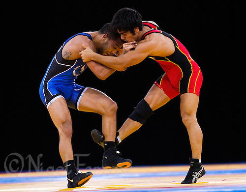 11 DEC 2011 - LONDON, GBR - Farzad Jafari (IRI) (in red) attempts to overpower Angel Escobedo (USA) (in blue) during the men's 55kg category final at the London International Wrestling Invitational and 2012 Olympic Games test event at the ExCel Exhibition Centre in London, Great Britain (PHOTO (C) NIGEL FARROW)