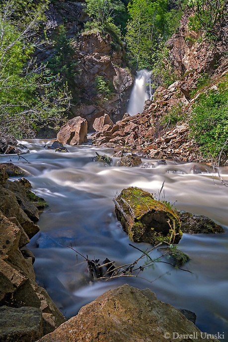 Fine Art Landscape Photograph of Hardy Falls In the Okanagan Valley of British Columbia Canada. The water rushing down the mountainside in the spring season is really fast, and can carry a lot of trees down the stream. This log was stuck to a rock as the waters rushed by.