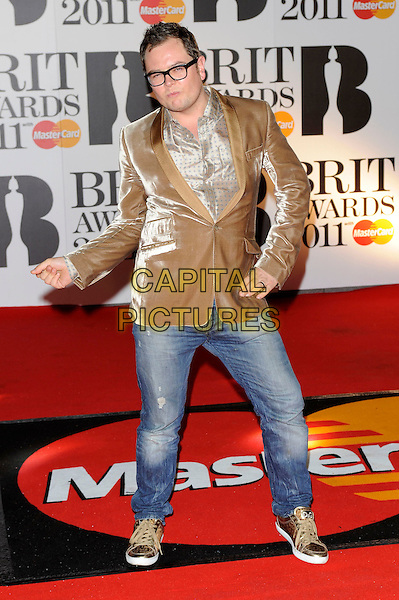 ALAN CARR.The BRIT Awards 2011 at the O2 Arena, London, England..February 15th, 2011.brits full length jeans denim gold brown beige velvet jacket glasses hands arms dancing funny posing shirt.CAP/FIN.©Steve Finn/Capital Pictures.