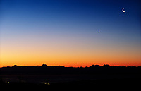 Alaska mountain range horizon, Mt. Deborah, Hess, Hayes (right to left) crescent moon and Venus, viewed looking south from Fairbanks on a December dawn, Fairbanks, Alaska