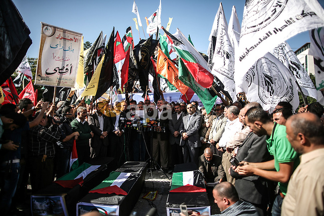 Members of the Palestinian factions hold national flags during a demonstration to show solidarity with Jerusalem and against the recent visits by Jewish activists to al-Aqsa mosque, in Gaza city November 9, 2014. In recent weeks there have been near-daily clashes between the stone-throwing Palestinians and Israeli riot police in occupied East Jerusalem. Some of the attacks have turned deadly. The unrest was triggered by Muslim fears of Jewish encroachment at the sacred site, a hilltop plateau known to Muslims as Haram as-Sharif, or Noble Sanctuary, and to Jews as the Temple Mount. Photo by Ali Jadallah