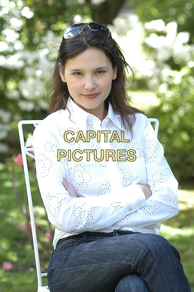"VIRGINIE LEDOYEN .Photocall for ""Un baiser s'il vous plait"" (Shall We Kiss?), Rome, Italy. .April 15th, 2008.half length white shirt arms crossed sitting holes cut out away pattern.CAP/CAV.©Luca Cavallari/Capital Pictures."