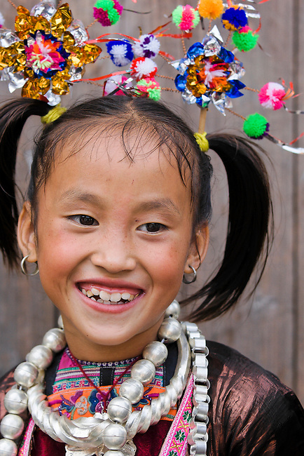 Young Dong girls dressed in their finest traditional clothes with large silver baubles and colorful headdresses.
