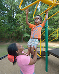 Three-year old Youel hangs on the bars with help from his mother, Tirhas Drar Brehane, in a playground in Durham, North Carolina. <br /> <br /> Refugees from Eritrea, the boy and his mother were resettled in Durham by Church World Service, which resettles refugees in North Carolina and throughout the United States.<br /> <br /> <br /> Photo by Paul Jeffrey for Church World Service.