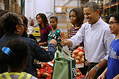 """(2nd R-L) United States President Barack Obama, first lady Michelle Obama, and their daughters Sasha Obama, 12, and Malia Obama, 15, help pack and distribute bags of food to needy children and seniors at the Capital Area Food Bank November 27, 2013 in Washington, DC. According to the White House, the first family was joined by family and friends and members of The Mission Continues, """"an organization of post-9/11 veterans who are awarded community service fellowships.""""  <br /> Credit: Chip Somodevilla / Pool via CNP"""