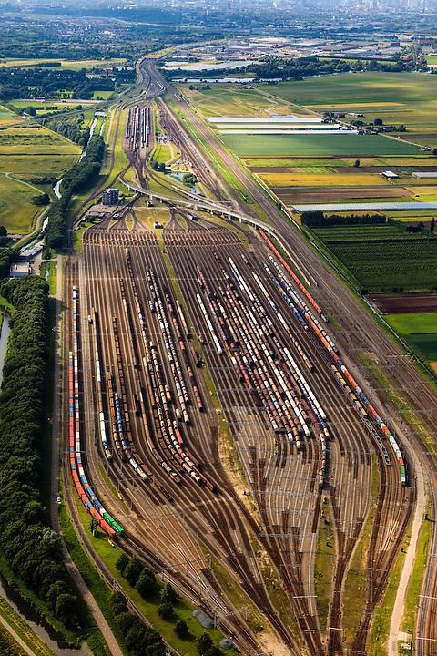 Nederland, Zuid-Holland, Zwijndrecht, 15-07-2012; Kijfhoek, rangeerterrein voor goederentreinen, overzicht van de verdeelsporen gezien richting Barendrecht. Rechts de reguliere spoorlijn..Kijfhoek huisvest Keyrail, exploitant Betuweroute en is in beheer bij ProRail. De Betuweroute, die begint als Havenspoorlijn op de Maasvlakte, verbindt via Kijfhoek de Rotterdamse haven met het achterland. Het rangeeremplacement dient voor het sorteren van goederenwagons waarbij gebruik gemaakt wordt van de zwaartekracht, het 'heuvelen': de wagons worden de heuvel opgeduwd, bij het de heuvel afrollen komen ze, door middel van wissels, op verschillende verdeelsporen. Railremmen zorgen voor het automatisch remmen van de wagons. Na het heuvelproces staan de nieuw samengestelde treinen op aparte opstelsporen..Kijfhoek, railway yard used by ProRail and Keyrail (Betuweroute operator). Kijfhoek connects via the Betuweroute (beginning as Havenspoorlijn on the Maasvlakte), through the port of Rotterdam with the hinterland. The shunting yard for sorting wagons makes use of gravity. The new trains are assembled on separate tracks..luchtfoto (toeslag), aerial photo (additional fee required).foto/photo Siebe Swart