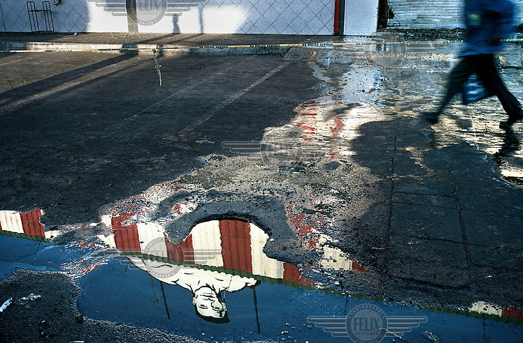A reflection of a building in a puddle caused by a water spillage in Groblersdal...