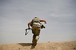 As their command post comes under attack a member of the 82nd Airborne, 1/508, Alpha Company, Third Platoon races to his gun position in Sangin, Helmand province, Afghanistan on Thursday, April 5, 2007. The firefight, less than 24 hours into the air assault on Sangin raged for over five hours.