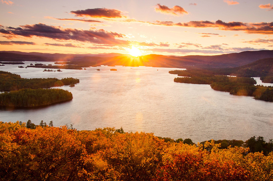 The sinking sun captured over Squam Lake in Autumn.