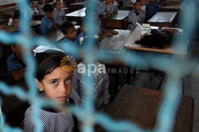 A Palestinian girl looks out of a classroom window as she attends a lesson on the first day of a new school year, at a United Nations-run school in Khan Younis in the southern Gaza Strip August 28, 2016. Photo by Ashraf Amra