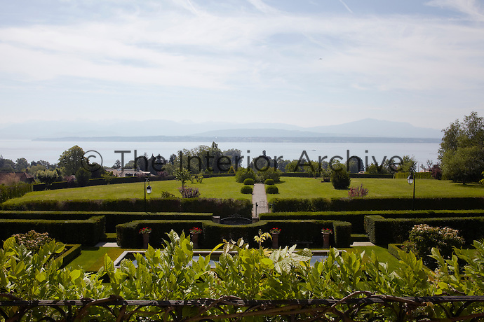 Viewed from the terrace the manicured gardens of the villa look out over Lake Geneva