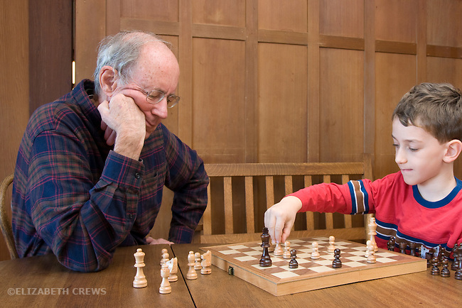 Berkeley CA Grandfather, seventy-six, playing chess with serious grandson, six-years-old MR